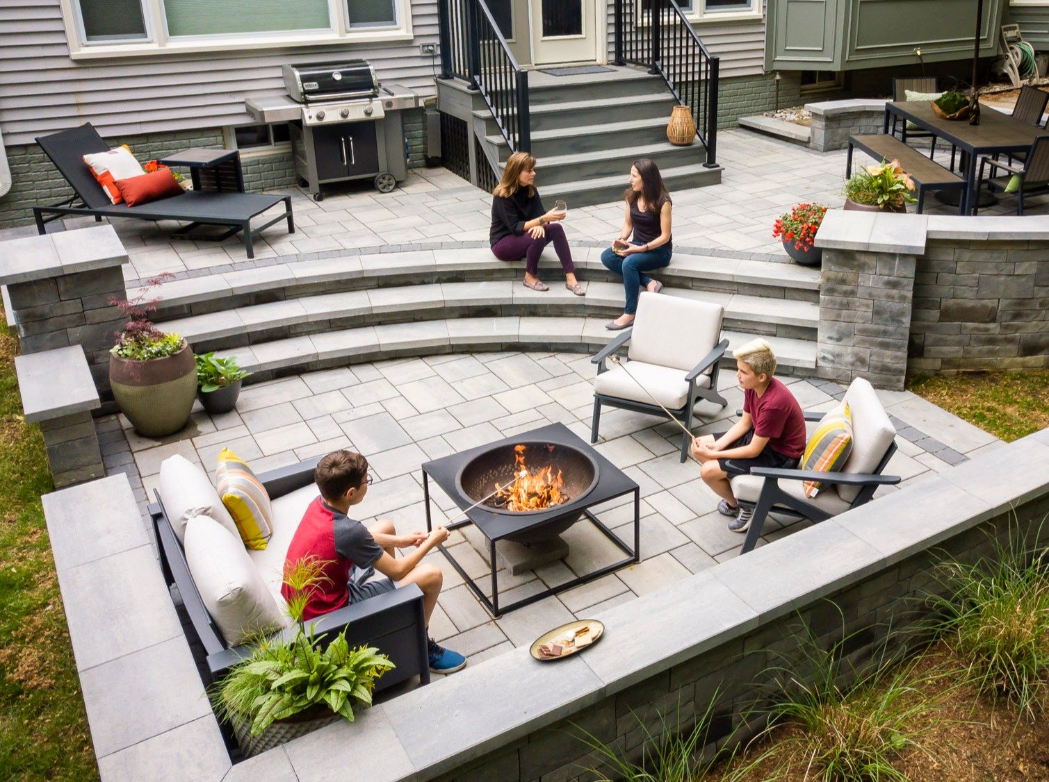 customers gathered around their fire pit and roasting marshmallows
