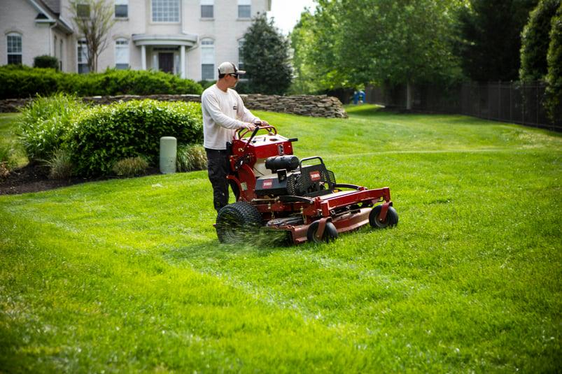 lawn care technician mowing lawn in Virginia