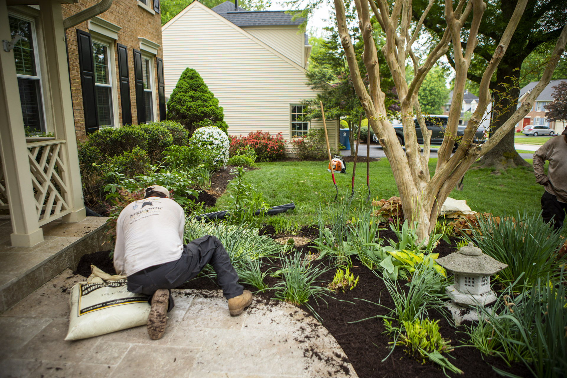 landscape technician applying mulch to keep plants healthy