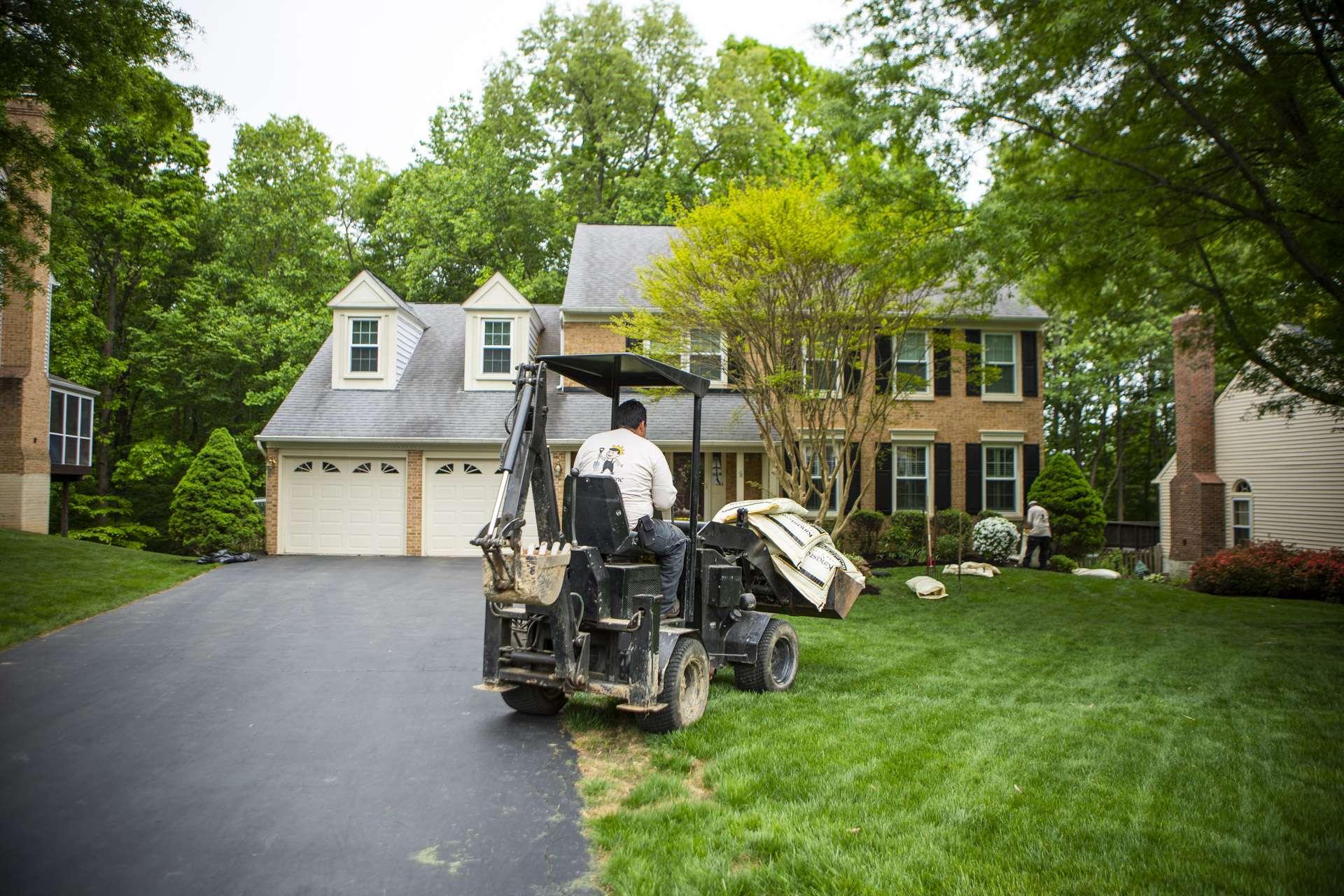 Landscape installation team driving a mini tractor