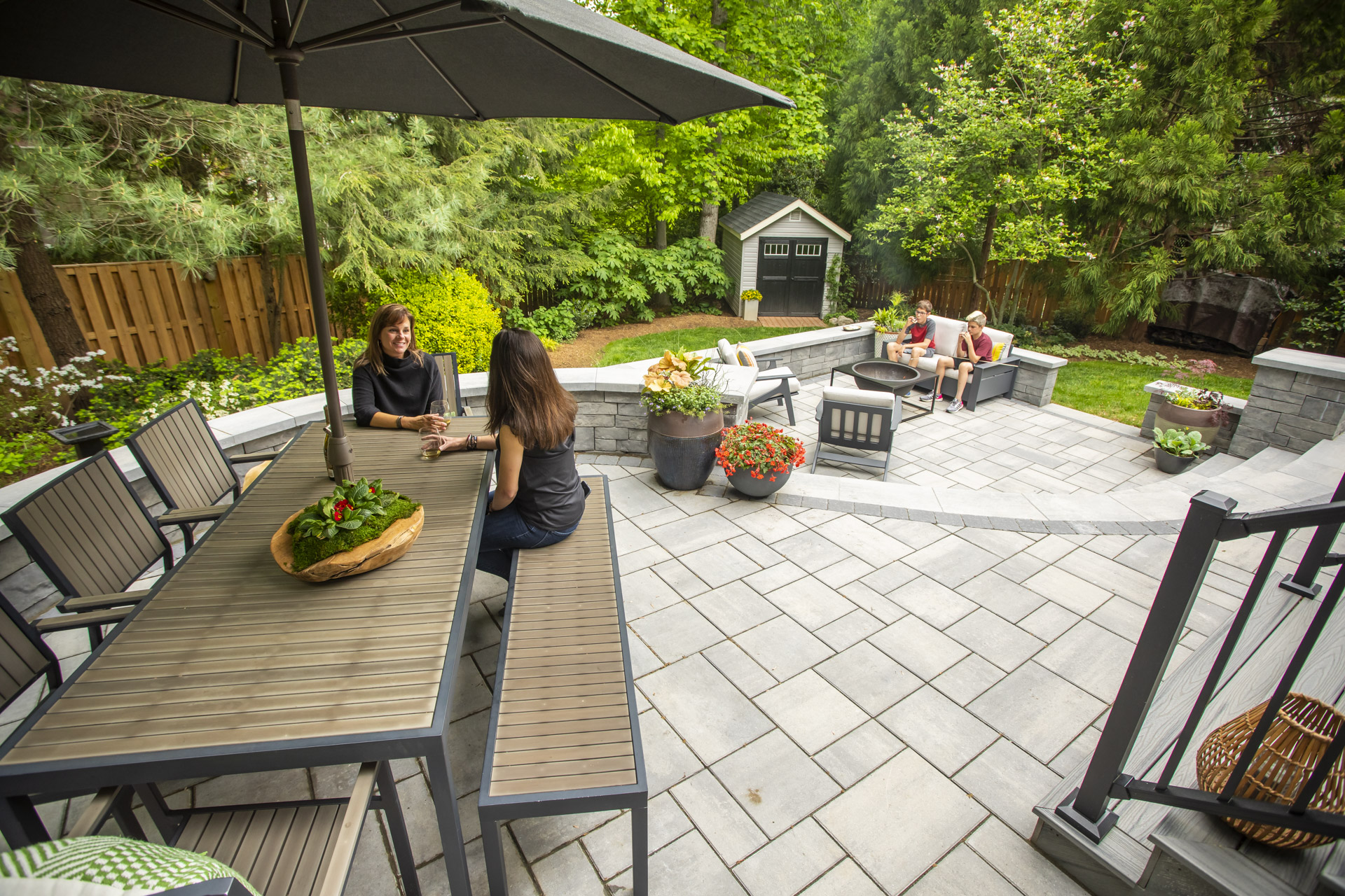 two-tiered patio with dining table and fire pit