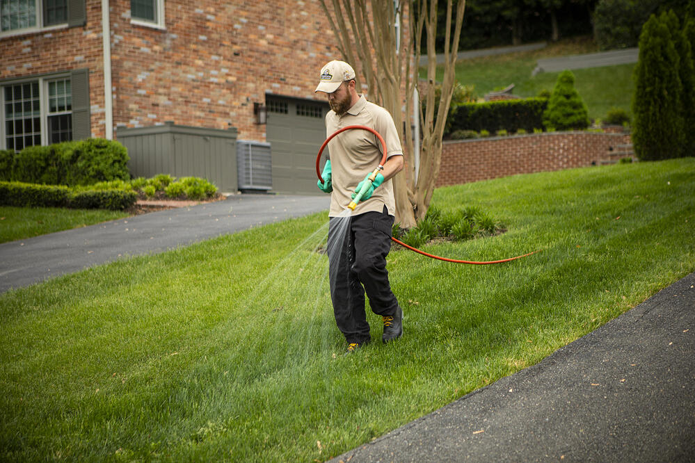 lawn care technician applying fall pre-emergent weed control