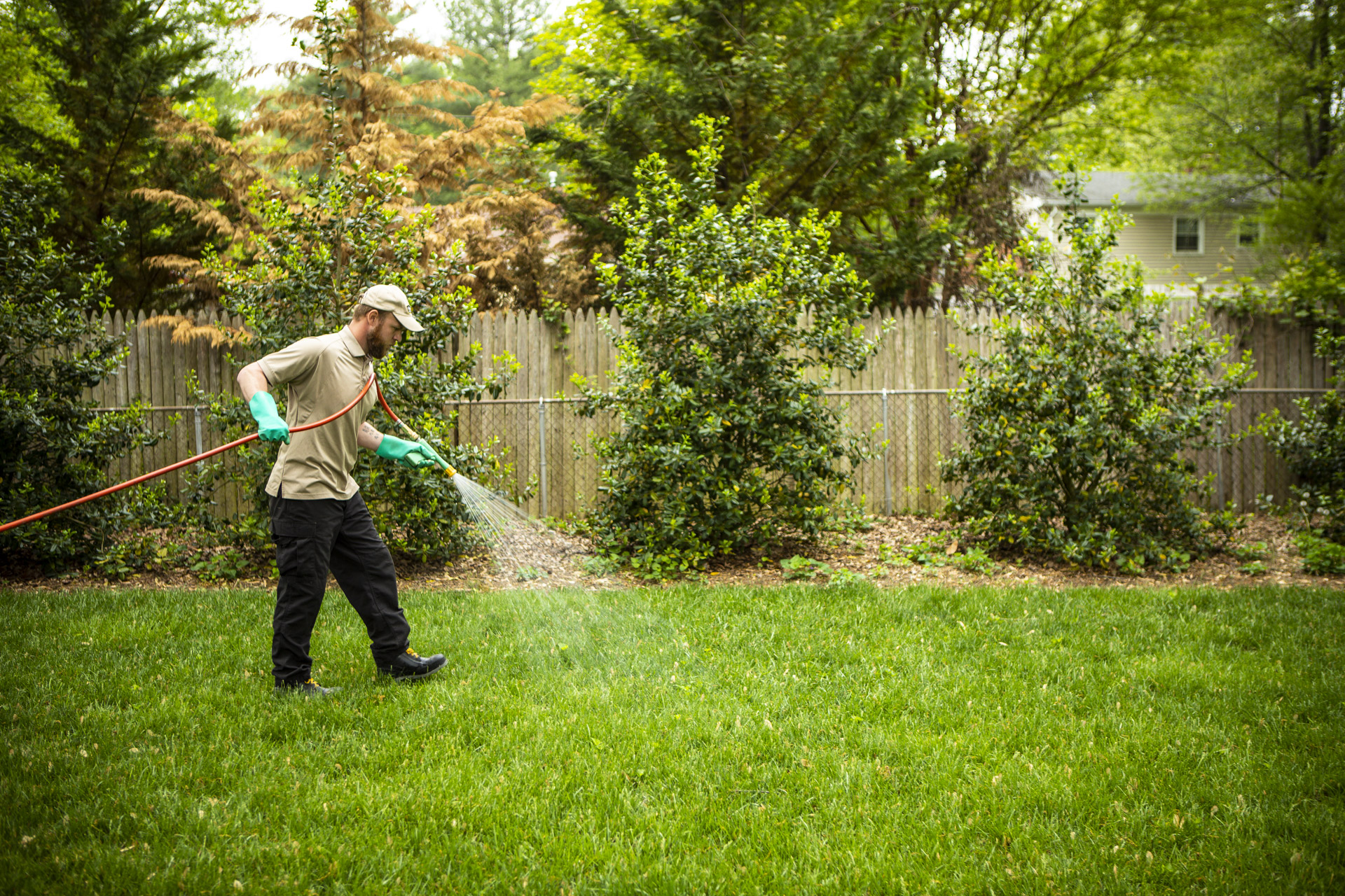 lawn care technician spraying weed control