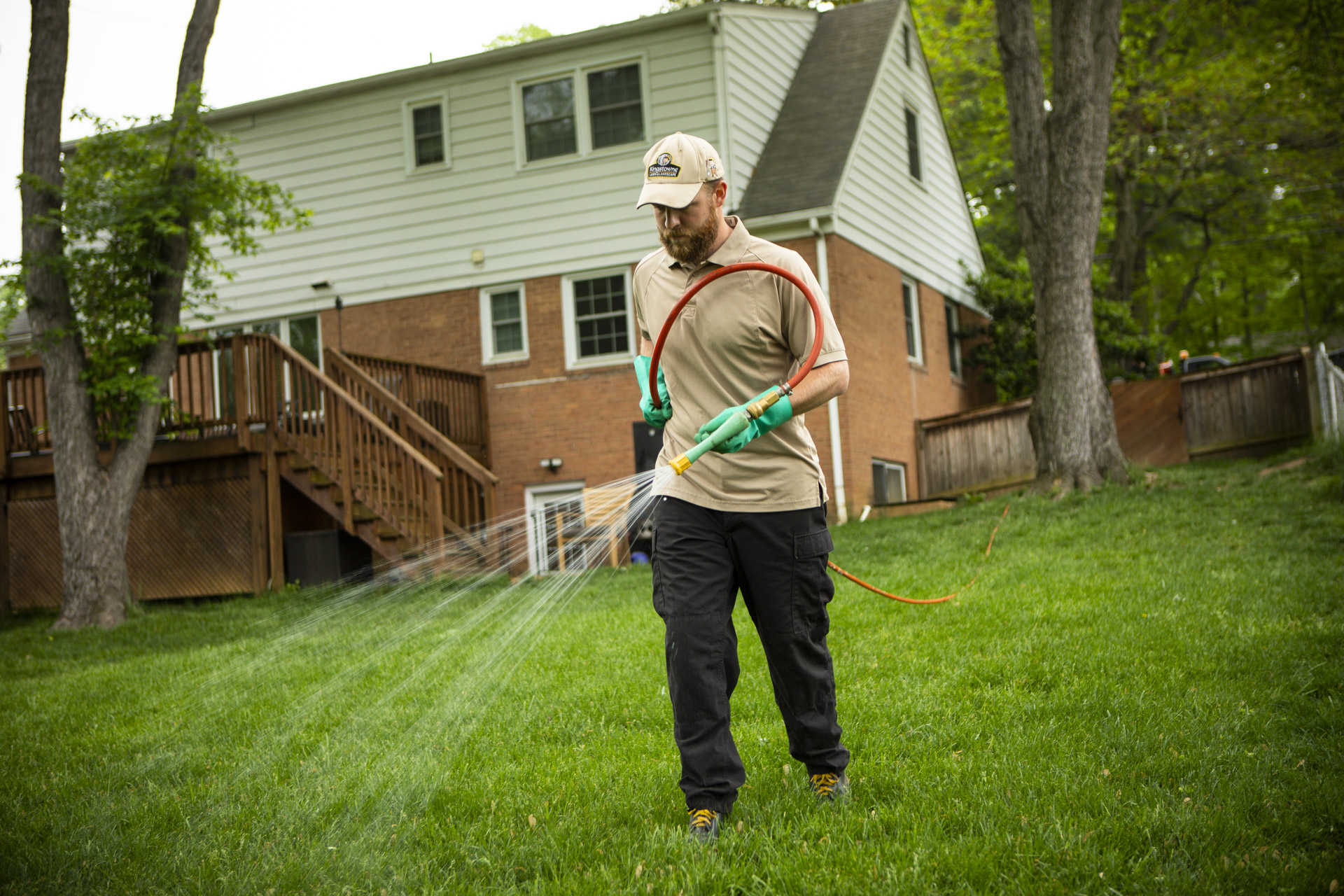 professional lawn care technician spraying lawn