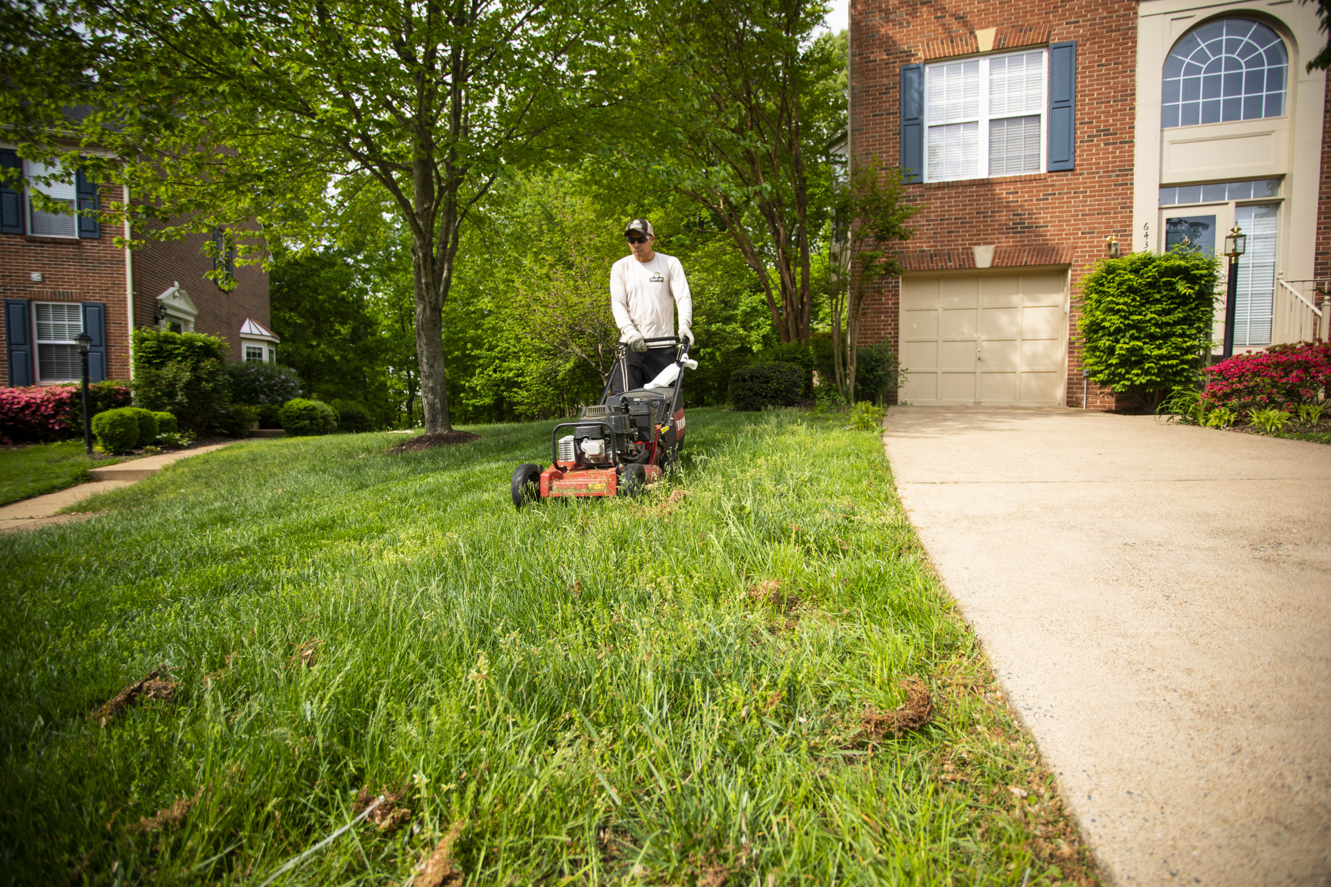 professional lawn technician mowing lawn