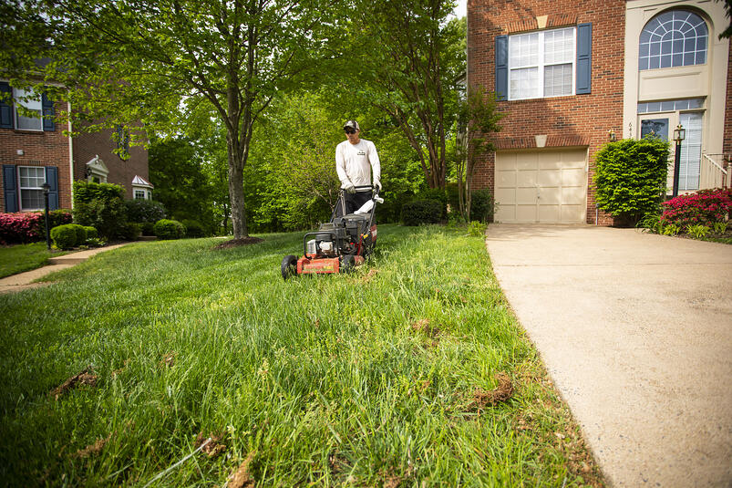 lawn care technician mowing lawn