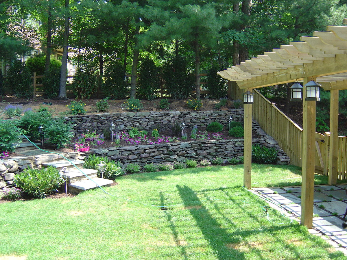 sloped backyard with retaining walls and plants