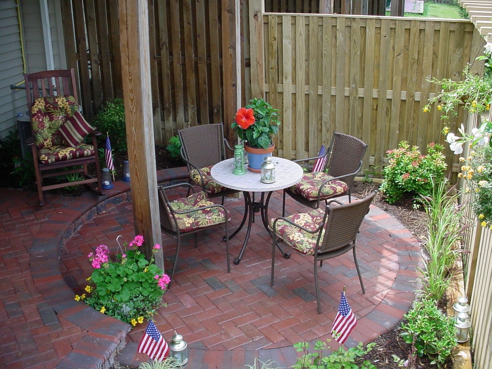 Enclosed townhouse patio with small plants and flowers