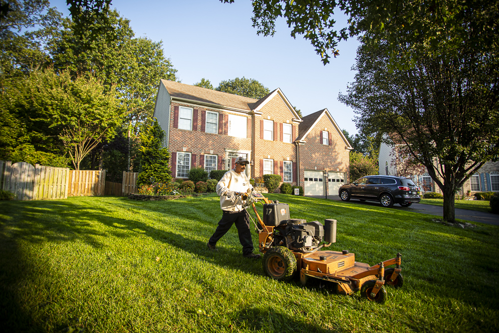 Lawn care team mowing a customers house weekly