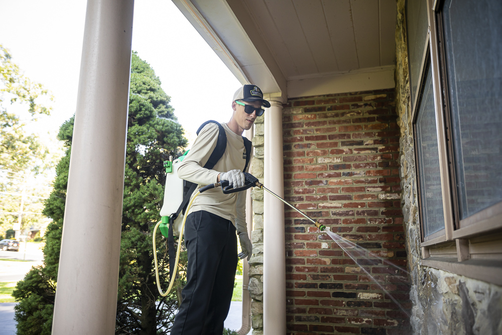 Pest control technician spraying the perimeter of a house
