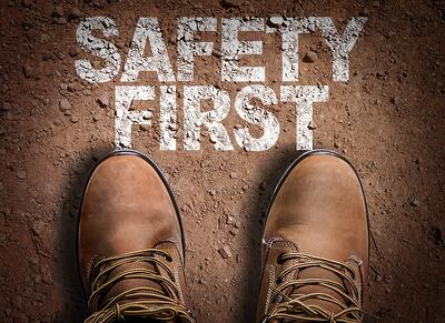 Boots and Safety First text on dirt