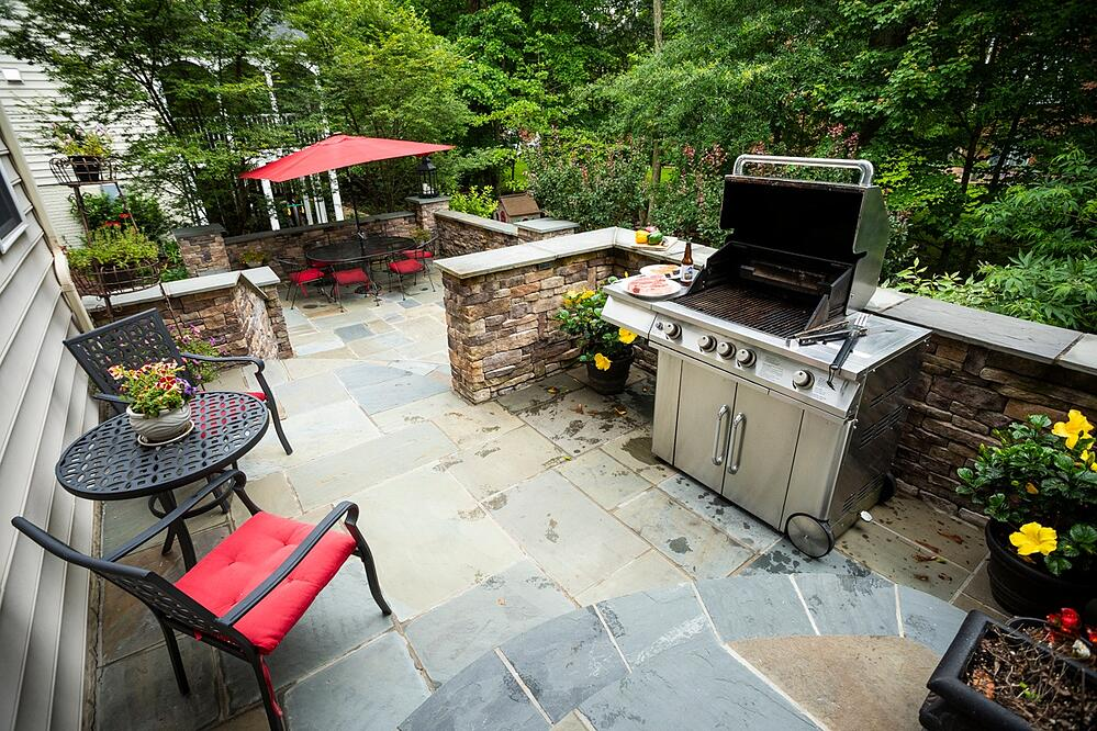 patio, grill, and dining area designed by Kingstowne Lawn & Landscape