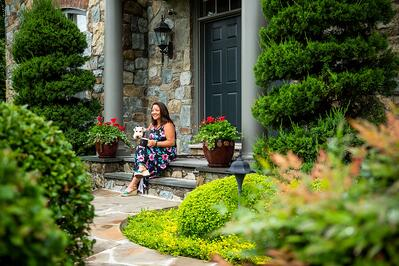 woman and dog on front porch surrounded by colorful plantings