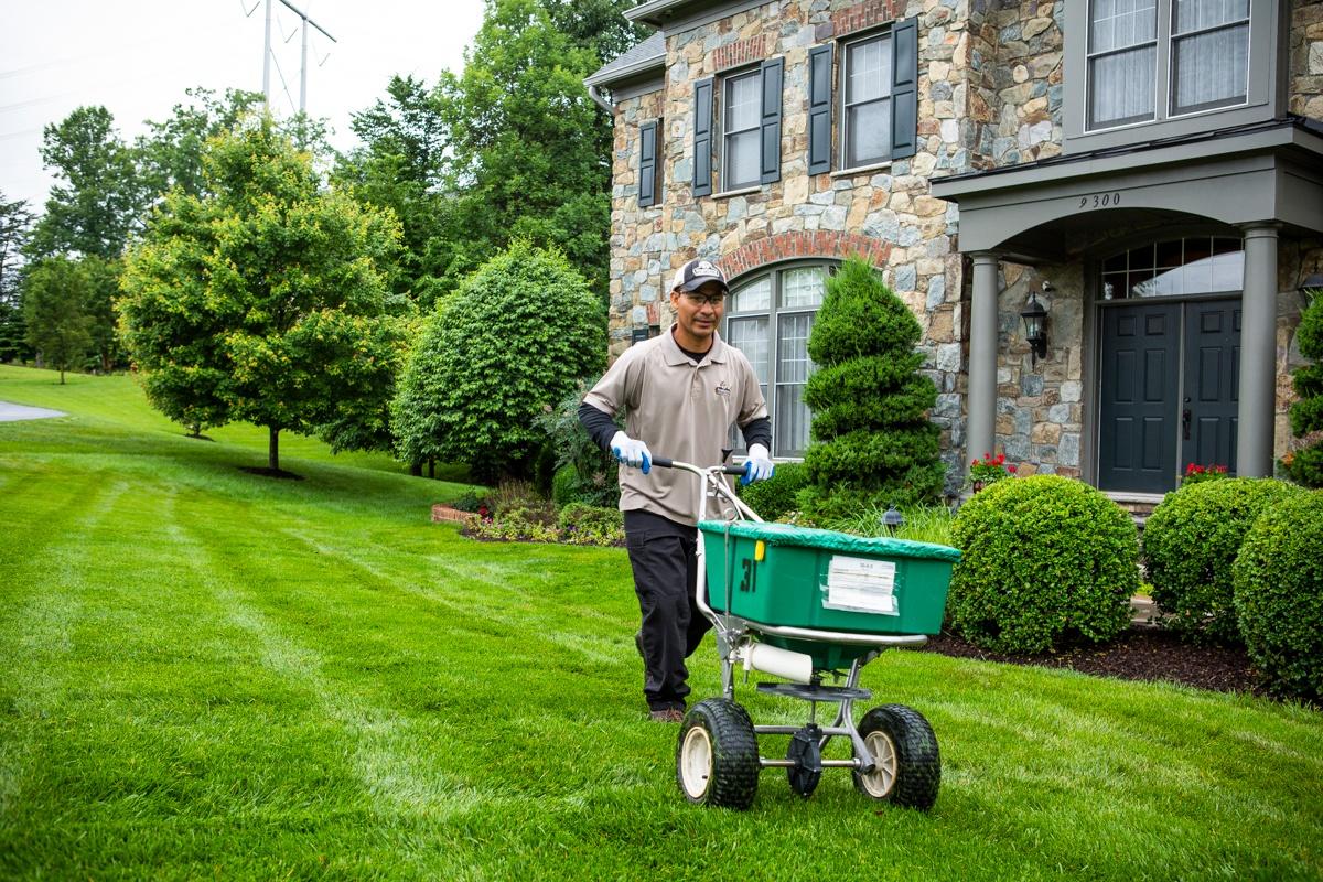 lawn care technician caring for lawn