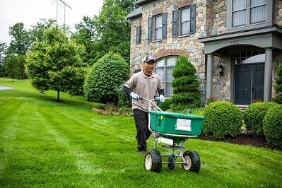 Technician performing lawn care treatment