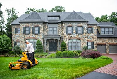 Technician performing lawn mowing  services