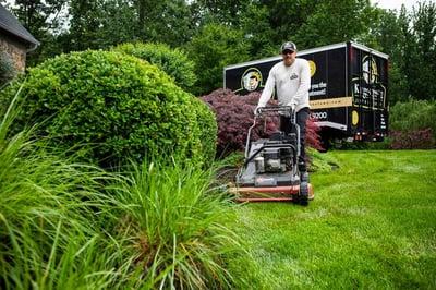 Kingstowne crew member mowing lawn