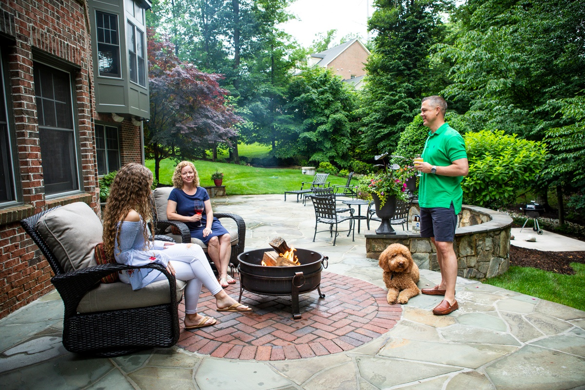 free-standing fire pit on patio with family and dog
