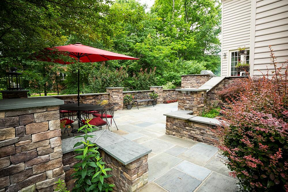 patio with retaining walls, dining area, plants and fountain