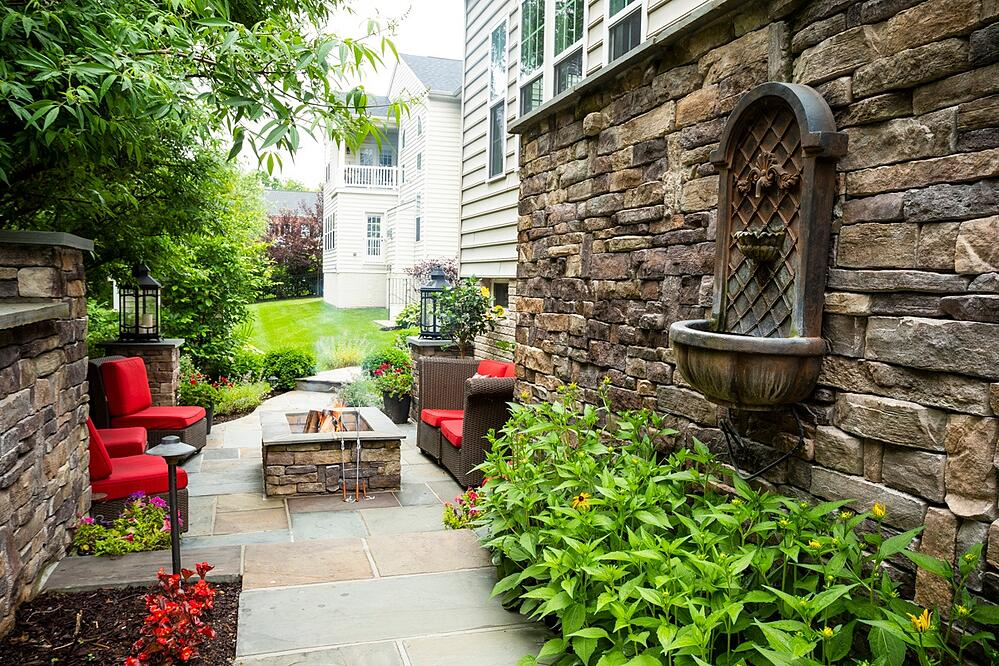 patio with wall, fountain, and fire pit designed by Kingstowne Lawn & Landscape