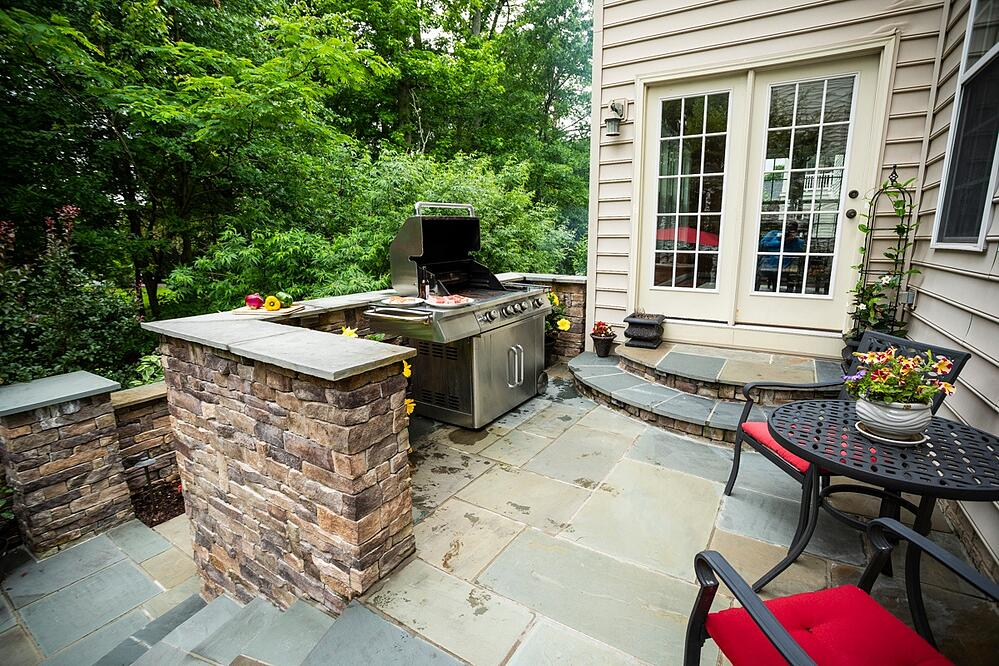 Patio in Alexandria, VA with grill, walls, and steps